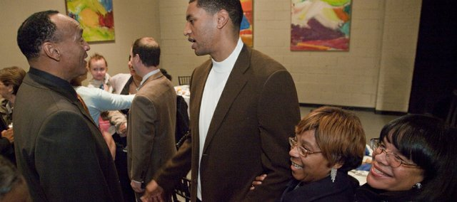 Former KU basketball greats Bud Stallworth, left, and Wayne Simien, visit, while Simien fans Eva Daniels, second from right, and Shelley Vann, far right, squeeze in for a photograph with Simien, Monday at the Martin Luther King Jr., community breakfast. Simien was the guest speaker at the fourth annual event.