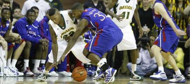 Kansas guard Josh Selby (32) swipes a steal from Baylor guard A.J. Walton during the first half. At right are Kansas guard Tyrel Reed and Baylor forward Anthony Jones (41).