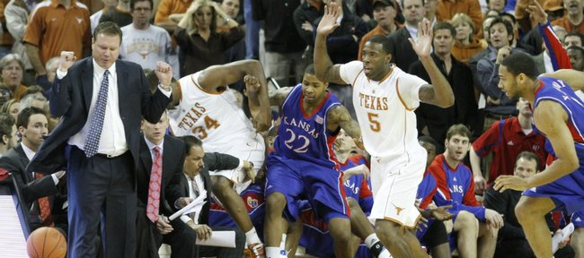 Kansas head coach Bill Self steers clear as Texas center Dexter Pittman (34) and Kansas forward Marcus Morris (22) crash into the Jayhawks bench going for a loose ball in the first half, Monday, Feb. 8, 2010 at the Frank Erwin Center in Austin.