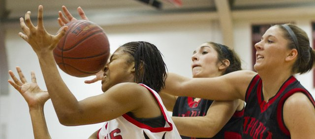 Lawrence High senior TaMiya Green, left, fights for a rebound with Emporia seniors Sarah Kolmer, center, and Courtney Waldner during Lawrence High's game against Emporia on Friday at LHS. EHS won, 44-29.
