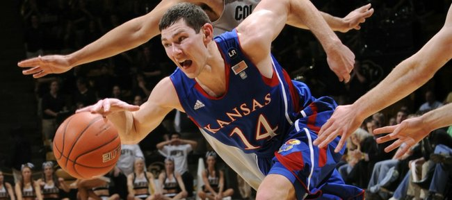 Kansas guard Tyrel Reed (14) drives past Colorado forward Marcus Relphorde during the first half Tuesday, Jan. 25, 2011, in Boulder, Colo.