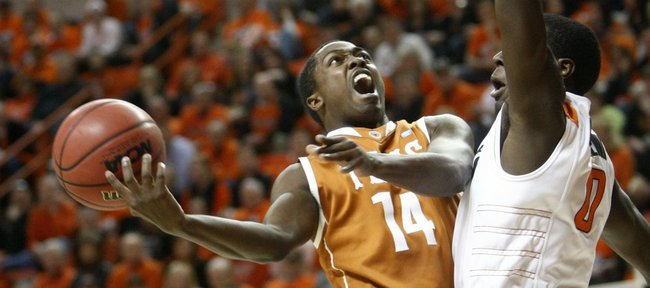 Texas guard J'Covan Brown, left, is fouled by Oklahoma State's Jean-Paul Olukemi, right, in the first half in Stillwater, Okla., Wednesday, Jan. 26, 2011.