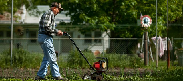 North Lawrence resident Leonard Holladay, 84, steadies his tiller as he works around his cold crops Wednesday. Many Lawrence residents are preparing their gardens for the planting of tomatoes and other summer vegetables.