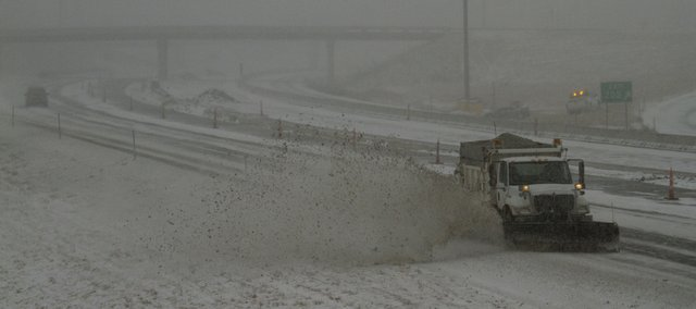 A Kansas Turnpike Authority snowplow clears an eastbound lane on I-70 at Michigan Street in Lawrence Tuesday Feb. 1, 2011. A total of about 8 inches of snow officially fell in the Douglas County area, with locally higher amounts reported.