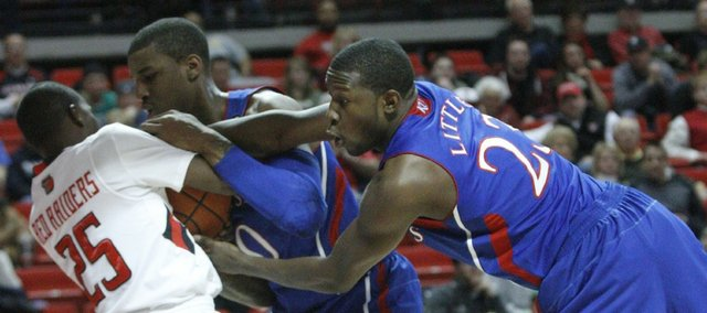 Kansas' Mario Little, right, and Thomas Robinson fight Texas Tech's David Tairu for a possession on Tuesday, Feb. 1, 2011 in Lubbock, Texas.