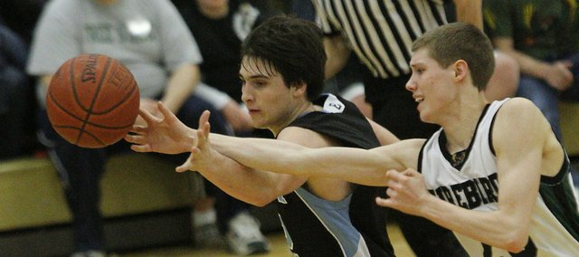 Free State's Tyler Self fights for a loose ball with Shawnee Mission East's Alex Schoegler in the second half on Friday, February 4, 2011 at FSHS.