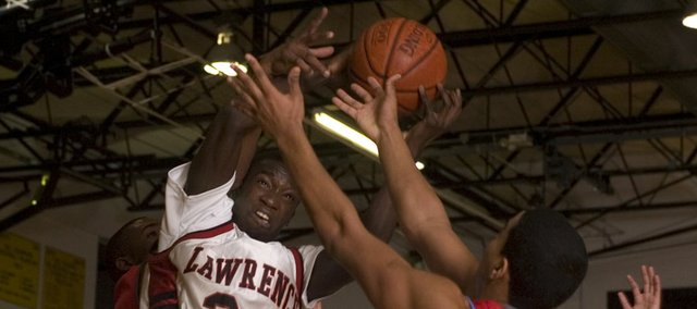 Lawrence High senior Baba Diallo (24) pulls in a rebound in this file photo. Diallo is playing Div. I basketball for Centenary.