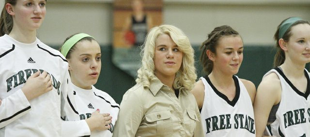 Free State's Paige Rothwell, center, who is injured, holds hands with teammates before the Firebirds tip off against Shawnee Mission East on Friday, Feb. 4, 2011 at FSHS.