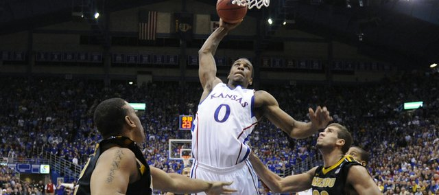 Kansas forward Thomas Robinson delivers a tomahawk jam between Missouri defenders Steve Moore, left, and Justin Safford during the second half on Monday, Feb. 7, 2011 at Allen Fieldhouse.