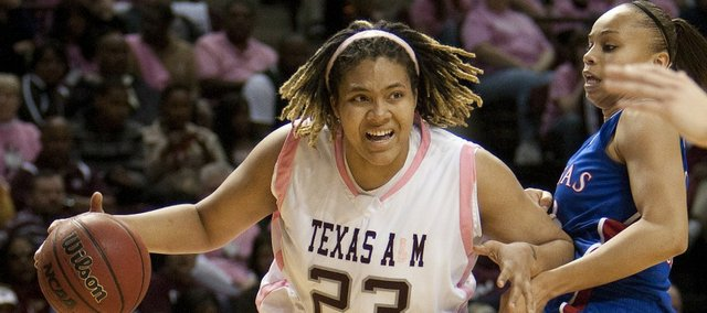 Texas A&M's Danielle Adams (23) drives on Kansas' Tania Jackson during the first half Saturday, Feb. 12, 2011, in College Station, Texas.