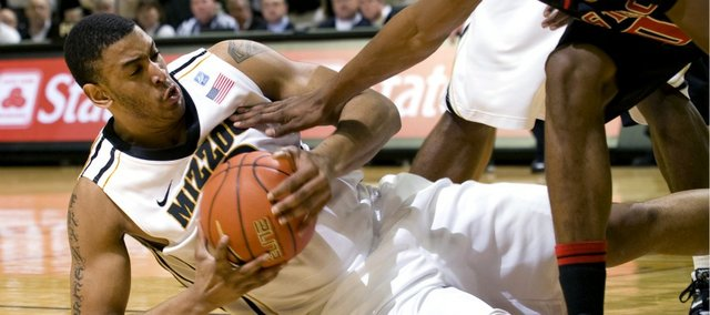 Missouri's Steve Moore, left, wrestles the ball away from Texas Tech's Jaye Crockett as he falls to the floor. The Tigers defeated the Red Raiders, 92-84, on Tuesday, Feb. 15, 2011 at Mizzou Arena in Columbia, Mo.