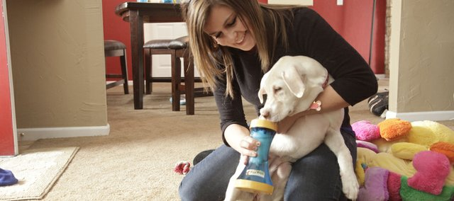 Cleaning her dog Callie's paws after a short walk, Kansas University sophomore Katie Mulich uses Paw Wash, a device she created when she was 12.
