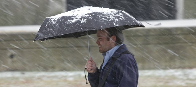 Will Bishop, a Kansas University graduate student from Boise, Idaho uses an umbrella to protecting himself from sleet falling on campus on Thursday, Feb. 24, 2011.