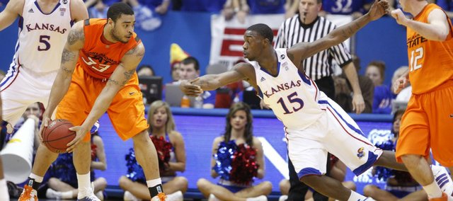 Kansas guard Elijah Johnson (15) takes a swipe at ball controlled by Oklahoma State forward Marshall Moses (33) during the first half on Monday, Feb. 21, 2011 at Allen Fieldhouse. At left is Kansas center Jeff Withey and at right is Oklahoma State guard Keiton Page.