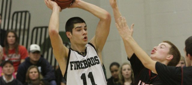 Free State's junior Georgi Funtarov (11) looks for help as he is guarded by Lawrence High's Logan Henrichs. Funtarov scored 30 points in the Firebirds' 58-57 victory Friday, Feb. 25, 2011 at FSHS.