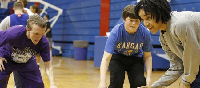 KU's Keena Mays, right, works with campers during a ball handling drill at the Special Olympics basketball clinic at Allen Fieldhouse on Sunday, Feb. 27, 2011.