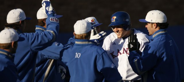Kansas' Chris Manship is greeted by his teammates after scoring against Iowa on Monday, Feb. 28, 2011 at Hoglund Ballpark.