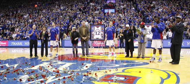 The Kansas University seniors and their families — from left, Tyrel Reed, Brady Morningstar and Mario Little — are showered with applause and flowers prior to tipoff of the Jayhawks' game against Texas A&M. KU won on Senior Night, 64-51, Wednesday, March 2, 2011 at Allen Fieldhouse.