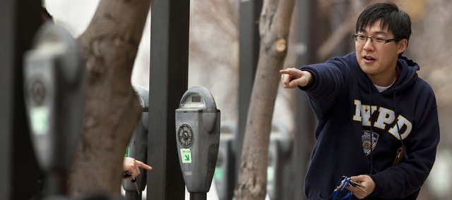 Kevin Lam, a Kansas University freshman from Overland Park, points his mother, Yuk Mei Wong, to the parking meter that corresponds to their parking space on Monday in the 700 block of Massachusetts Street. The amount of parking tickets issued in downtown Lawrence dropped by about 14 percent in 2010.
