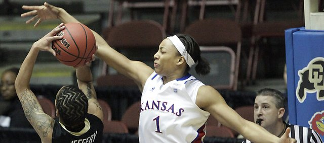 Kansas forward Aishah Sutherland goes to block a shot by Colorado's Chucky Jeffery in the first game of the Big 12 women's tournament in Kansas City on Tuesday. KU won the game, 71-45.