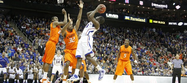 Kansas forward Mario Little hangs for a bucket and a foul against the Oklahoma State defense late in the second half on Thursday, March 10, 2011, at the Sprint Center in Kansas City, Mo. Little converted the free throw, which ultimately proved to be enough to give the Jayhawks the victory.