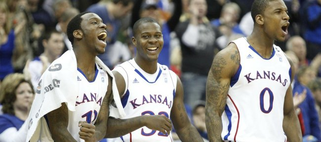 Kansas players Tyshawn Taylor, left, Josh Selby and Thomas Robinson celebrate a bucket and a foul created by teammate Mario Little against Oklahoma State with time dwindling in the second half on Thursday, March 10, 2011 at the Sprint Center in Kansas City.