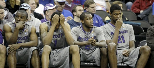 Kansas State players Martavious Irving, left, Shane Southwell (1), Devon Peterson (2) and Jordan Henriquez-Roberts (21) sit on the bench in the final moments of Colorado's 87-75 victory over KSU on Thursday, March 10, 2011, in Kansas City, Mo.
