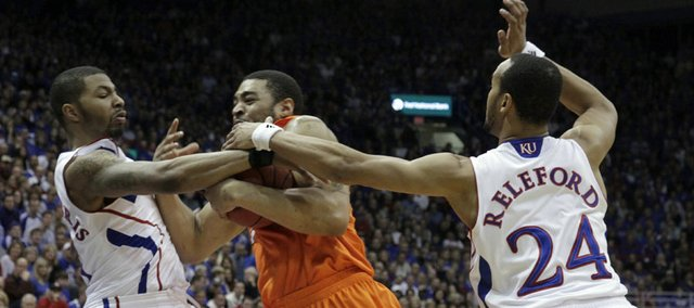 Marcus Morris (left) and Travis Releford tangle with Marshall Moses as Kansas and Oklahoma State played during the first half Monday, Feb. 21, 2011, at Allen Fieldhouse