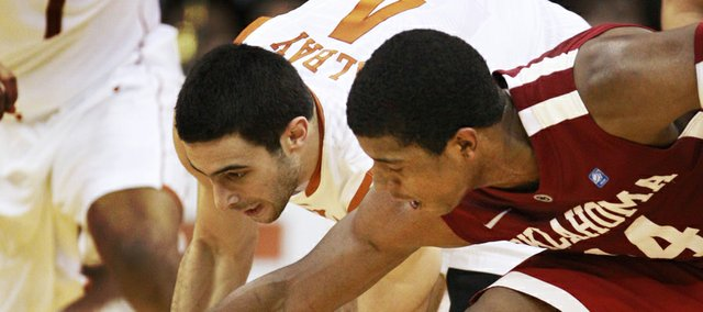 Texas guard Dogus Balbay (4) scoops up the ball while covered by Oklahoma's Carl Blair, right, during the first half of Thursday's Big 12 men's basketball tournament in Kansas City, Mo. UT defeated OU, 74-54.