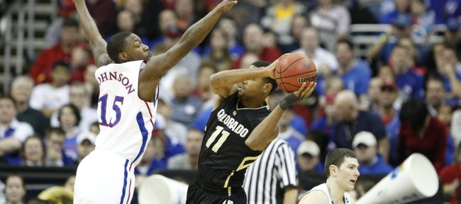 Kansas guard Elijah Johnson defends a pass by Colorado guard Cory Higgins during the first half Friday, March 11, 2011 at the Sprint Center.