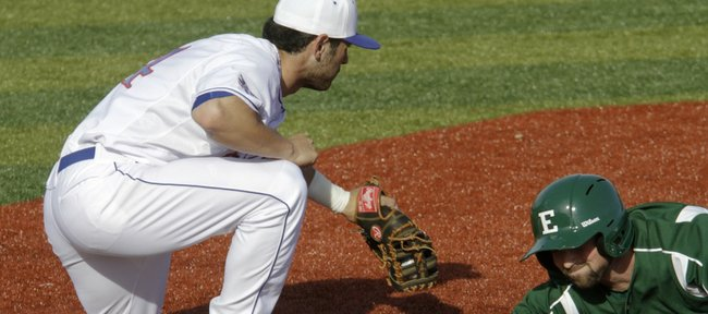 Jake Marasco, left, comes within inches of tagging out an Eastern Michigan runner on a pick-off attempt. Marasco and Kansas rolled to an 8-2 victory on Friday, March 11, 2011 at Hoglund Ballpark.