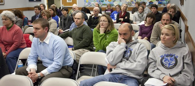 District parents, concerned about their neighborhood schools, listen to the Lawrence school board's discussion on how to move forward on a task force's recommendations to close or consolidate schools.