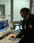 Rachelle Preston, a corrections officer at the Douglas County Jail, monitors activity from inside central control in this January 2007 photo. The Douglas County Commission approved the $187,270 purchase of a new security system for the jail Wednesday.