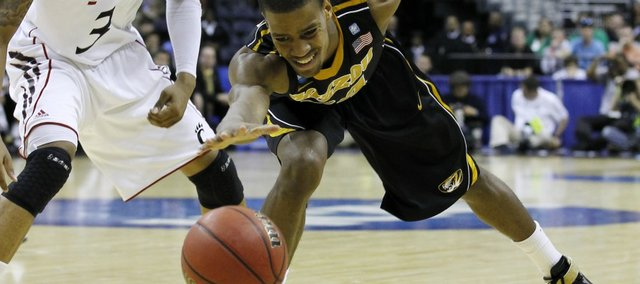 Missouri guard Kim English chases a loose ball as Cincinnati guard Dion Dixon looks on during the first half of the West regional second round NCAA tournament college basketball game, Thursday, March 17, 2011, at the Verizon Center in Washington.