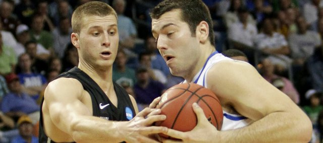 Princeton's Dan Mavraides (33) tries to take the ball away from Kentucky's Josh Harrelson, right, during the first half of an East Regional second round NCAA tournament college basketball game in Tampa, Fla., Thursday, March 17, 2011.