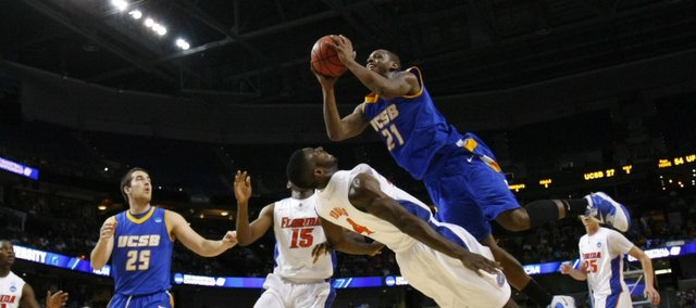 UC Santa Barbara's James Nunnally (21) runs into Florida's Patric Young (4) during the second half of a Southeast regional second-round game in Tampa, Fla., Thursday, March 17, 2011.
