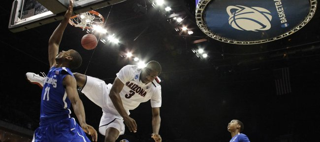 Arizona guard Kevin Parrom tumbles to the ground trying to block a shot by Memphis forward Wesley Witherspoon in the first half of a West Regional NCAA tournament second round college basketball game, Friday, March 18, 2011 in Tulsa, Okla.