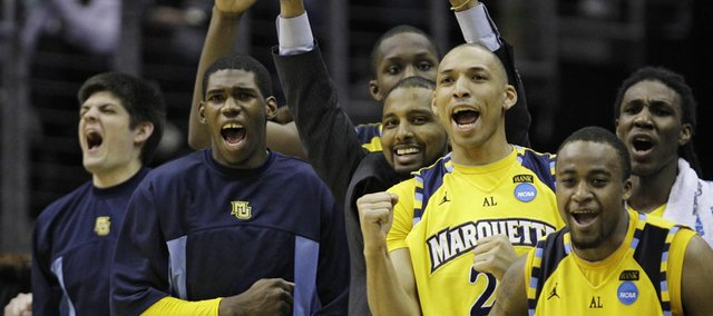 Marquette players react in the first half of an East regional NCAA college basketball tournament second round game against Xavier Friday, March 18, 2011, in Cleveland.