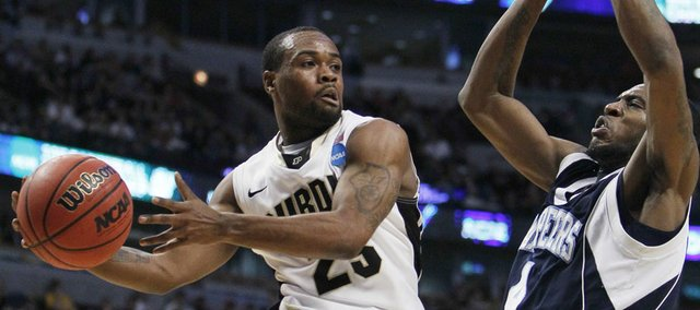 Purdue's Lewis Jackson (23) looks to pass under pressure from St. Peter's Ryan Bacon (4) in the first half of a second-round NCAA Southwest Regional tournament college basketball game in Chicago, Friday, March 18, 2011.