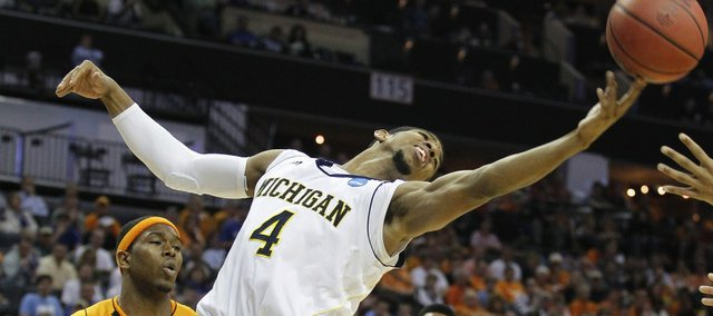 Michigan guard Darius Morris (4) reaches for a loose ball as Tennessee guard Cameron Tatum, left, looks on during the second half of a West Regional NCAA tournament second round college basketball game, Friday, March 18, 2011, in Charlotte, N.C.