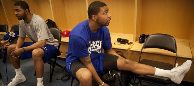 Kansas forward Marcus Morris watches the Kentucky Princeton game as his brother Markieff Morris takes questions from media members in the locker room during a day of practices and press conferences for teams playing second and third round games in Tulsa on Thursday, March 17, 2011 at the BOK Center.