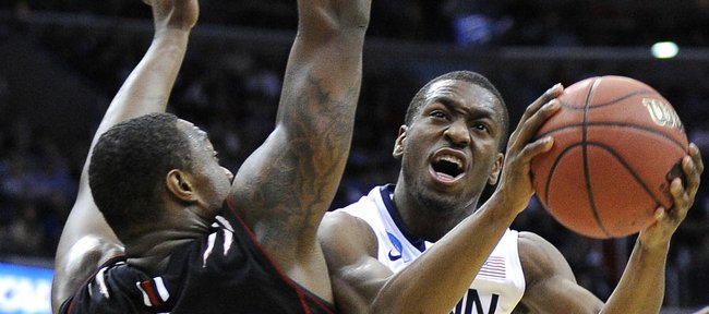 Connecticut guard Kemba Walker, right, shoots around Cincinnati forward Yancy Gates during the first half of the West Regional third-round NCAA tournament college basketball game, Saturday, March 19, 2011, at the Verizon Center in Washington.