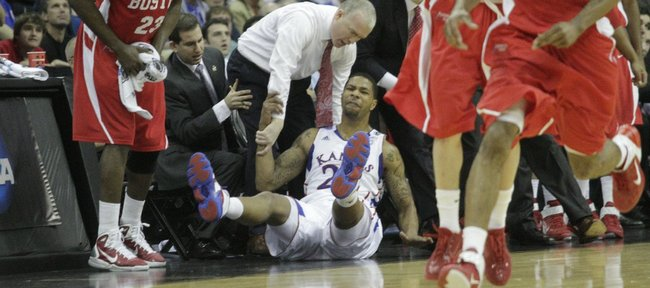Boston University coach Patrick Chambers reaches down to catch KU's Marcus Morris after Morris missed a last second three-point to end the first half.