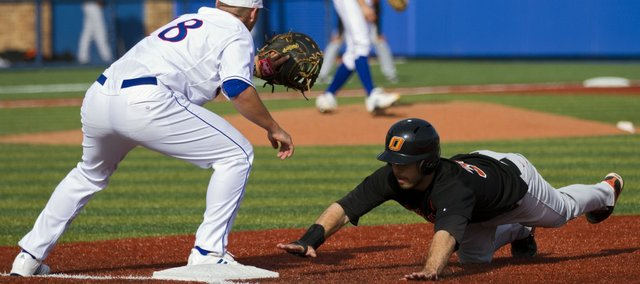 Oklahoma State's Davis Duren, right, beats the throw to first baseman Zac Elgie, left, in the first inning. The Cowboys beat the Jayhawks, 3-1, on Friday at Hoglund Ballpark.
