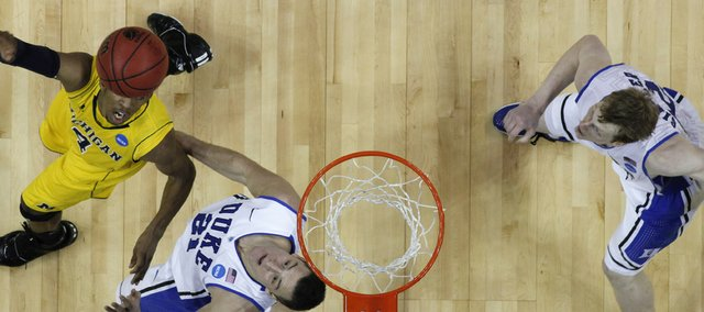 Duke forward Miles Plumlee (21) and Michigan guard Darius Morris (4) wait for the ball as Duke forward Kyle Singler, right, looks on in the second half of a West Regional NCAA tournament third-round college basketball game, Sunday, March 20, 2011, in Charlotte, N.C.