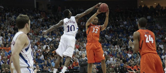 Kansas guard Tyshawn Taylor defends Illinois' Demetri McCamey's shot Sunday, March 20, 2011 at the BOK Center in Tulsa, Okla.