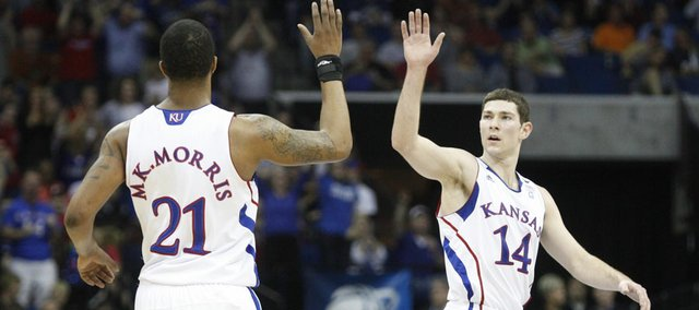 Kansas guard Tyrel Reed high fives forward Markieff Morris after a three by Morris against Illinois during the first half on Sunday, March 20, 2011, at the BOK Center in Tulsa.