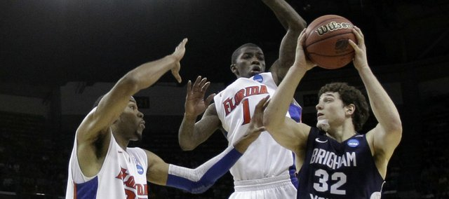 BYU's Jimmer Fredette (32) looks to pass while being defended by Florida's Alex Tyus (23) and Kenny Boynton (1) during overtime of the NCAA Southeast regional college basketball semifinal game Thursday, March 24, 2011, in New Orleans.