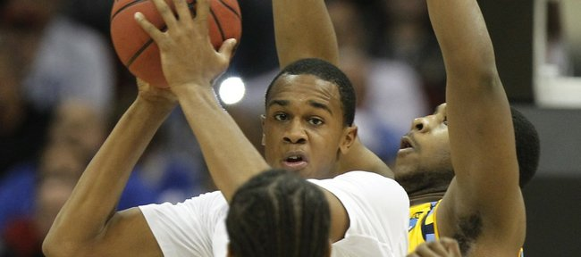 North Carolina's Dexter Strickland (1) passes theball away from Marquette's Junior Cadougan, right, and teammate Dwight Buycks (23) during the first half of an an East regional semifinal game in the NCAA college basketball tournament Friday, March 25, 2011, in Newark, N.J.