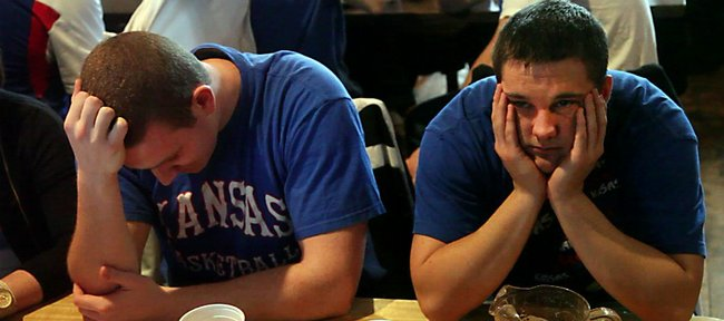 KU seniors Patrick Watkins, Holton, left, and Jay Ryan, of Garden City, can't contain their disappointment at Johnny's Tavern, 401 N. Second St., during Sunday's game against Virginia Commonwealth University. Kansas fans filled local bars to take in the game between No. 1-seed KU and No. 11-seed VCU, but the mood soured early as the Rams dominated the game. KU lost 71-61.